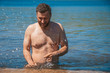 Bearded man in water drops on the beach
