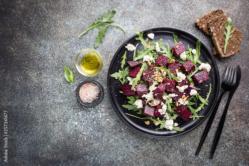 Fototapeta beetroot salad with blue cheese, arugula and walnut in a black plate on stone background, top view obraz