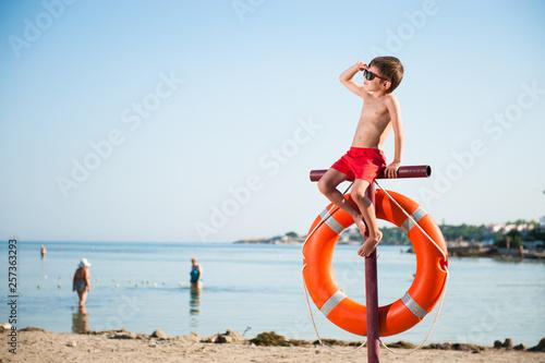 Photo beautiful small kid in sunglasses sitting on pole with orange lifebuoy hanging o