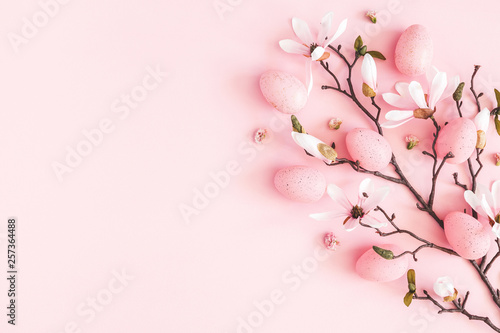 Easter composition. Easter eggs, pink flowers on pastel pink background. Flat lay, top view, copy space