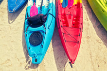 Multi Colored Kayaks With Padd...