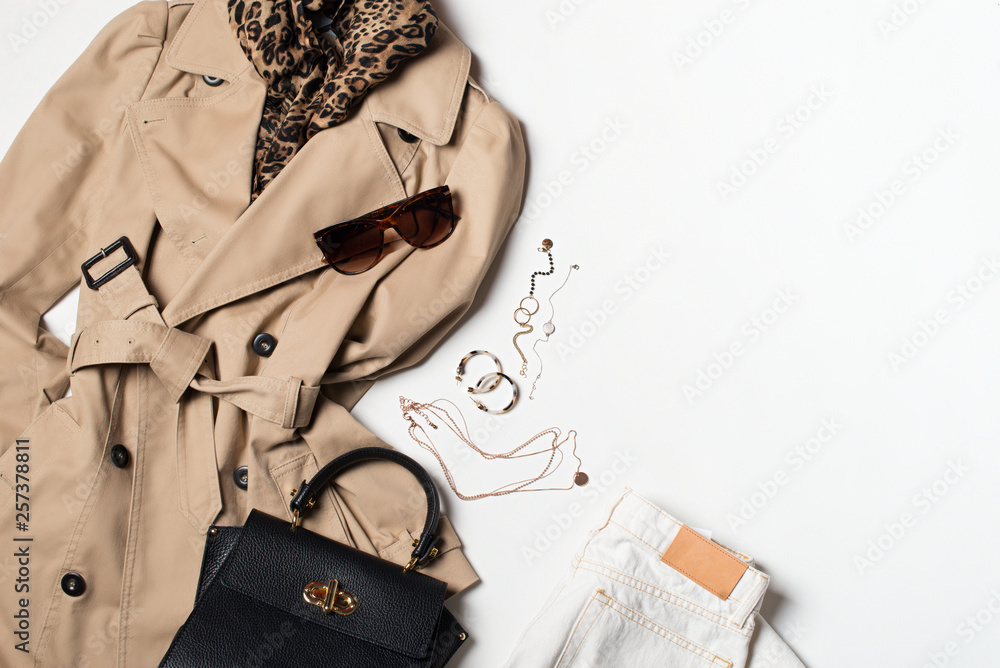 Fototapeta Women fashion clothes and accessories flat lay, beige trench coat with bag, glasses, denim and western boots