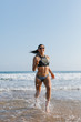 Fit young woman in bikini running at the beach into the sea splashing water drops. Outdoor fitness, healthy lifestyle and summer freedom concept.