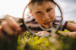 Leinwandbild Motiv Boy looking through magnifying glass