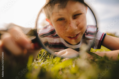 Fotografía  Boy looking through magnifying glass