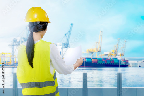 Canvas Print Rear view of asian worker woman with yellow hard hat looking at paperwork on the