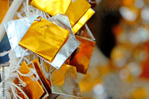 Photographie  Silver and gold color glossy paper tied with white thread hanging in funfair for