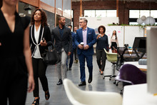 Businesspeople Arriving For Work In Busy Modern Open Plan Office