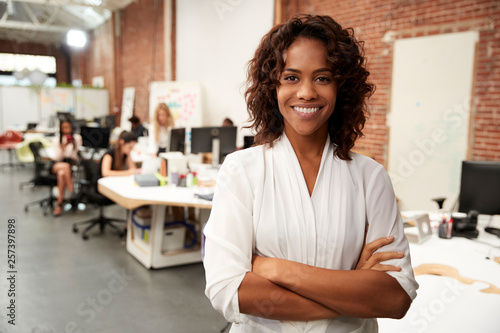 Fotografia  Portrait Of Businesswoman In Modern Open Plan Office With Business Team Working