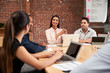 Young Businesswoman Leading Office Meeting Around Table