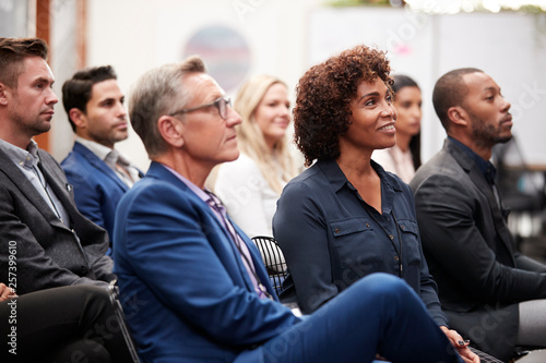 Group Of Businessmen And Businesswomen Listening To Presentation At Conference Wallpaper Mural