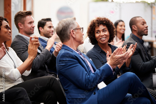 Fototapeta Group Of Businessmen And Businesswomen Applauding Presentation At Conference