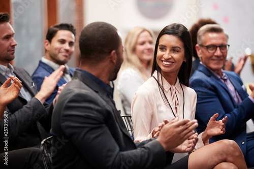 Foto  Group Of Businessmen And Businesswomen Applauding Presentation At Conference