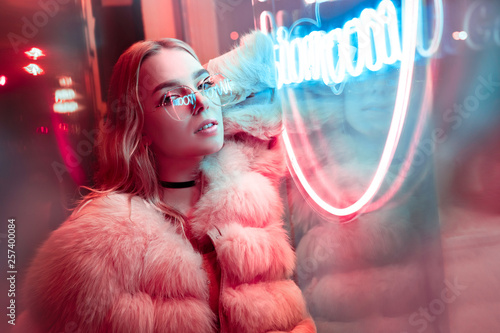 Fotografia  Teen hipster girl posing near neon sign on street, portrait