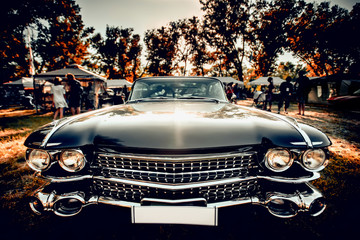 Close-up wide-angled photo of black vintage retro car with shining chrome radiator grille, bumper and headlamps
