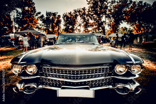 Fototapeta Close-up wide-angled photo of black vintage retro car with shining chrome radiat