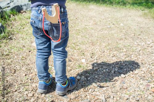 Fotografie, Tablou  3 years little boy shooting wooden slingshot