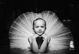 Czarno-białe zdjęcie uroczej uśmiechniętej baleriny w białej spódniczce baletnicy i koronie leżącej na podłodze z rękami pod brodą. Piękna mała dziewczynka kłaść w ładnej spódniczce baletnicy na czarnym tle. - 257404026