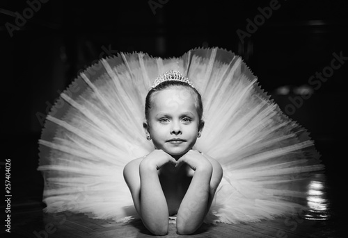 Black and white photo of a cute smiling ballerina in white tutu and a crown laying on the floor with hands under the chin Fototapet