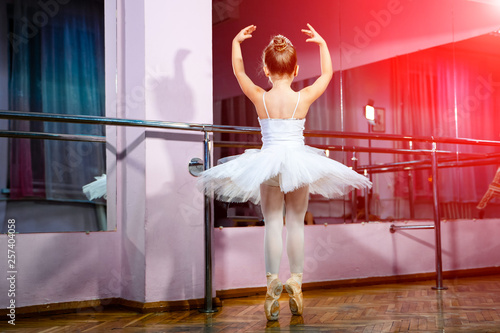Obraz na plátně Adorable little ballerina in a white tutu and tights standing in pose in front of the mirror in studio