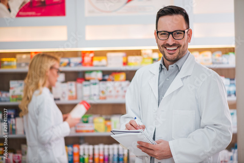 Keuken foto achterwand Apotheek Medicine, pharmaceutics, healthcare and people concept. Portrait of a handsome smiling pharmacist, female colleague working in the background.
