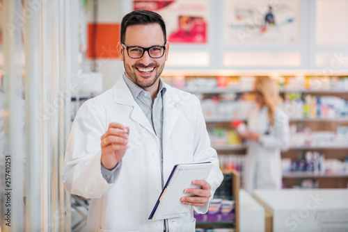 Poster Pharmacie Portrait of a handsome pharmacist with clipboard, smiling at camera.