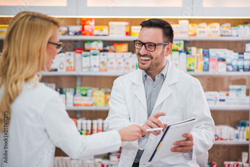 Photo sur Aluminium Pharmacie Two cheerful pharmacists working together.