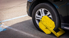 Yellow Tire Clamp On A Tire. Penalty And Fine For Improper Parking.