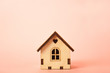 Miniature wooden house on a pink background close-up and copy space