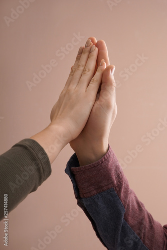 Fotomural  Young man and woman touching palms against color background