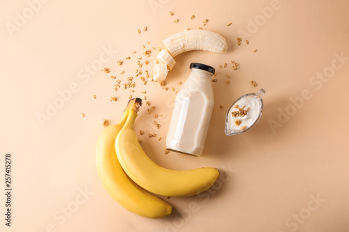 Leinwand Poster Composition with bottle of banana smoothie on color background