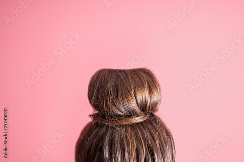 Fototapeta Young woman with hair bun on color background obraz