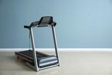 Modern Treadmill Near Color Wall In Gym