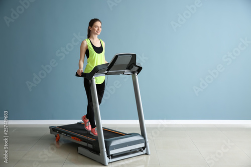 Sporty young woman training on treadmill in gym Fototapeta