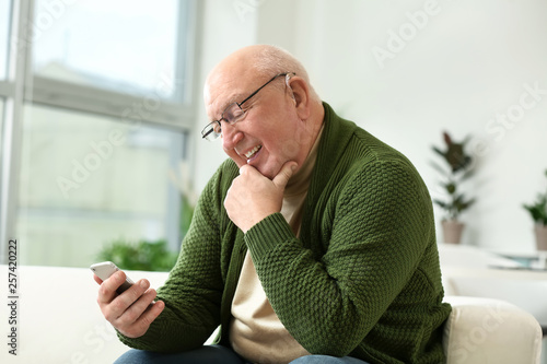 Senior man with hearing aid using mobile phone at home Canvas Print