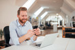 Positive ginger businessman using smartphone while sitting at the desk with laptop.