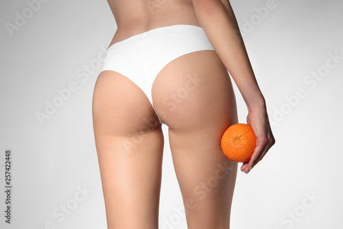 Fotografie, Obraz Beautiful young woman with orange on light background