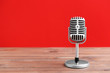 Leinwanddruck Bild - Retro microphone on table against color background
