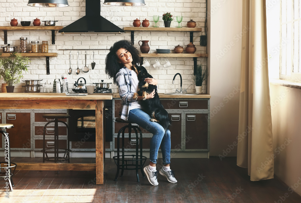 Fototapety, obrazy: African-American woman with cute funny dog in kitchen