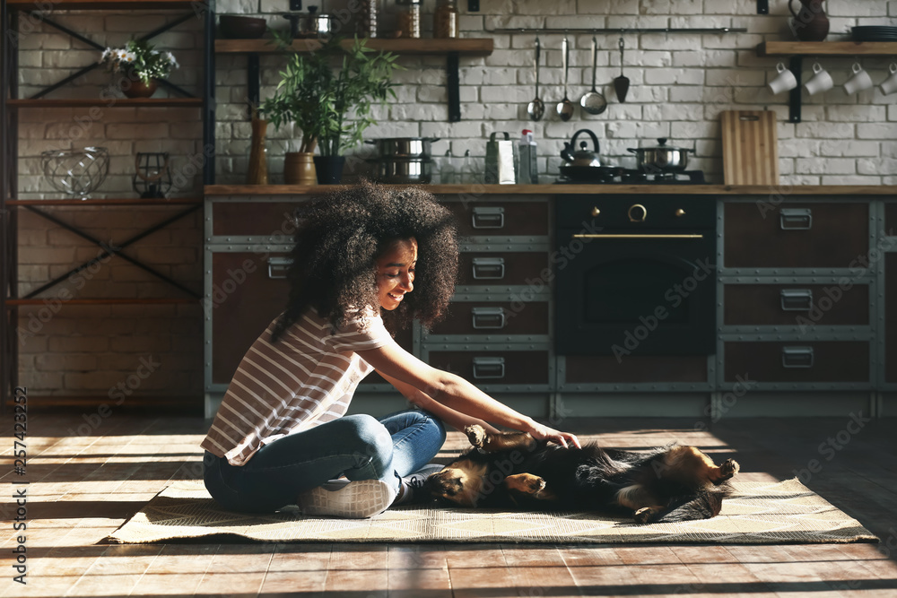 Fototapety, obrazy: African-American woman with cute funny dog at home