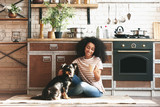 Fototapeta Zwierzęta - African-American woman with cute funny dog drinking coffee in kitchen