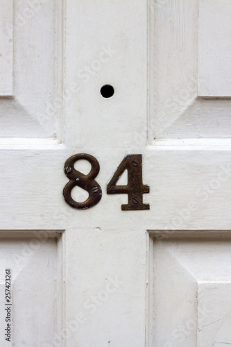 Fotografia  House number 84 with the eighty-four on a white door