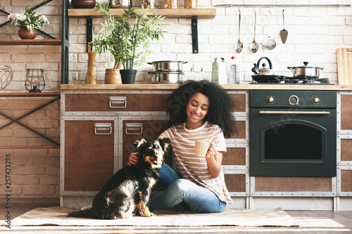 African-American woman with cute funny dog drinking coffee in kitchen - 257423286