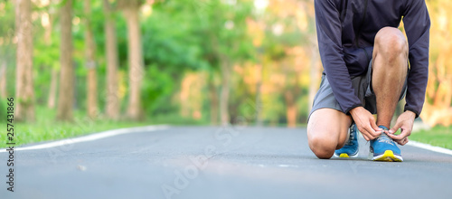 Foto  Young athlete man tying running shoes in the park outdoor, male runner ready for jogging on the road outside, asian Fitness walking and exercise on footpath in morning