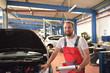 Portrait freundlicher Automechaniker in einer Werkstatt zur Reparatur von KFZ // Portrait of a friendly car mechanic in a workshop for the repair of motor vehicles