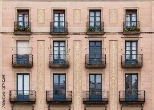 Canvas Print Windows and balconies in row on facade of historic building