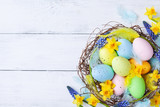 Сolorful Easter eggs in nest, feather and spring flowers on white table top view. Holiday card or banner. - 257442890
