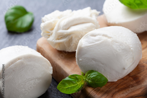 Fotografía Mozzarella cheese with basil on wooden board