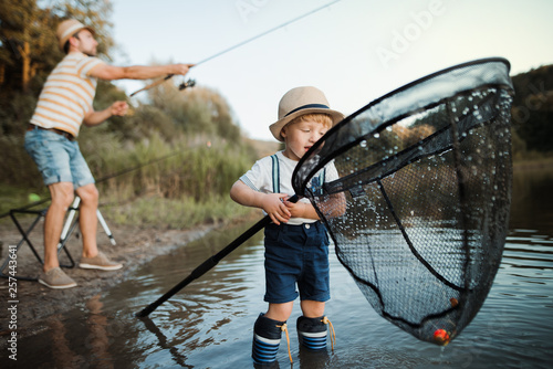 Poster de jardin Peche A mature father with a small toddler son outdoors fishing by a lake.