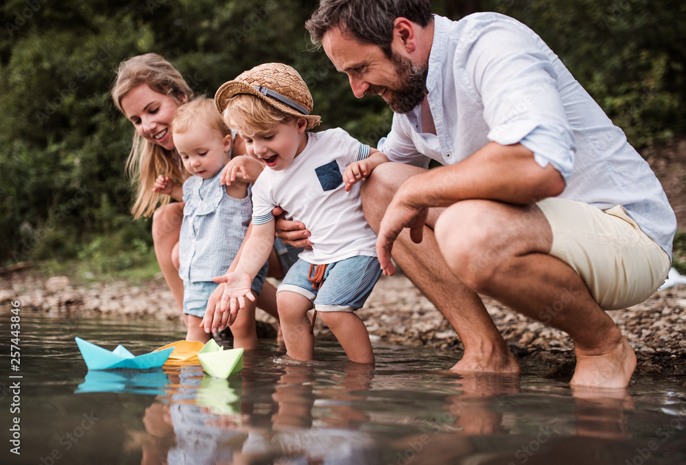 Fototapety, obrazy: Young family with two toddler children outdoors by the river in summer, playing.